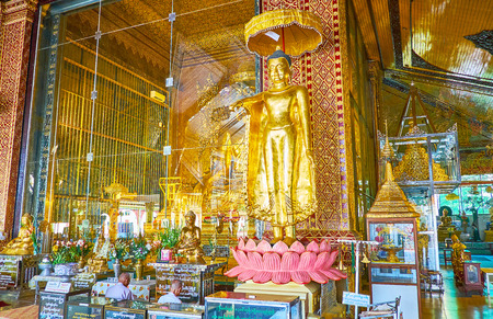YANGON, MYANMAR - FEBRUARY 27, 2018: The golden statues of Lord Buddha in Kyay Thone Pagoda, decorated with fine ornaments and carvings, on February 27 in Yangon.
