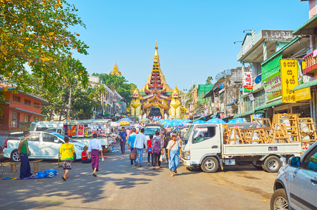 YANGON, MYANMAR - FEBRUARY 27, 2018:  The busy market in front of the East Gate of Shwedagon, decorated with huge statues of leogryph guards and the pyatthat multistaged roof, on February 27 in Yangon.