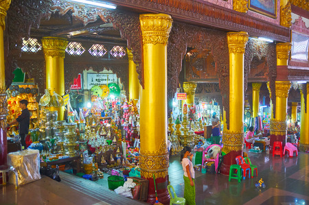 YANGON, MYANMAR - FEBRUARY 27, 2018:  The scenic hall of East Gate path to Shwedagon Pagoda with huge gilt columns, carved wooden decorations and relief patterns, on February 27 in Yangon. Editorial