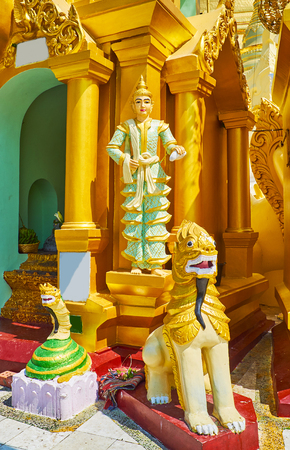 The group of religious statues at the small outer stupa of Shwedagon Zedi Daw: the Naga-Raja snake, Chinthe leogryph and Nat Spirit sculpture on background, Yangon, Myanmar.