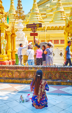 YANGON, MYANMAR - FEBRUARY 27, 2018: Pilgrims perform the Buddha Bathing religious ritual at Thursday Corner of Plantetary Posts at Shwedagon Pagoda, on February 27 in Yangon. Editorial