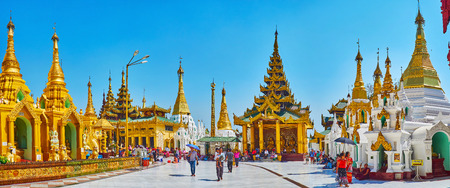 YANGON, MYANMAR - FEBRUARY 27, 2018:  Panorama of Shwedagon Zedi Daw with pilgrims in circle alley, bright golden stupas and the image house with intricate pyatthat roof, on February 27 in Yangon Redakční