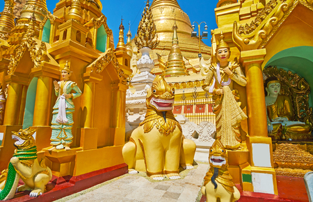 The mythic animals (chinthe leogryphs, nagar serpents) and Nat Spirit statues among the shrines with Shwedagon main pagoda on the background, Yangon, Myanmar