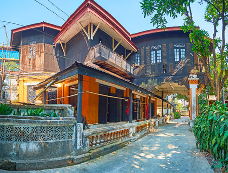 The old Colonial style wooden house at the Chaukhtatgyi Buddha Temple with cells of Bhikkhu monks and shady gren garden around it, Bahan township, Yangon, Myanmar.