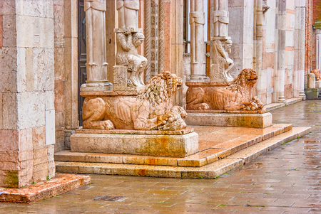 The sculptures of the lions with atlases made from different colors of marble located at the main entrance to Ferrara Cathedral, Italy