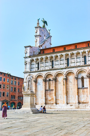 LUCCA, ITALY - APRIL 30, 2013: The richly decorated exterior of San Michele in Foro Basilica with bling arcades on its sides, on April 30 in Lucca