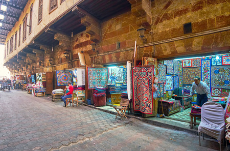 CAIRO, EGYPT - DECEMBER 21, 2017:  The line of stalls in Tentmakers alley (Sharia Khayamiya) with large amount of handmade appliqued and embroidered fabric pieces, on December 21 in Cairo, Egypt.