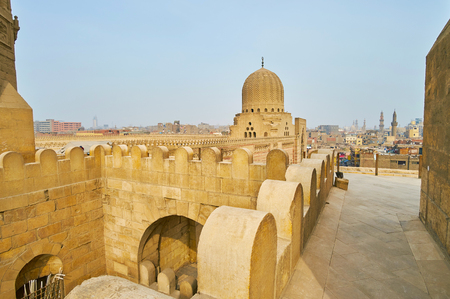The battlements on the top of scenic meideval Bab Zuwayla Gate, located adjacent to the Sultan Al-Muayyad mosque with carved zigzag dome, Cairo, Egypt.