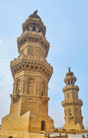 The ornate towers of medieval Bab Zuwayla Gate, decorated with carved Islamic patterns and muqarnas details under the balconies, Cairo, Egypt.