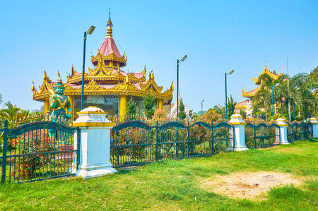 The small pavilion with decorated carved roof located on the territory of Kyauktawgyi Pagoda in Mandalay, Myanmar