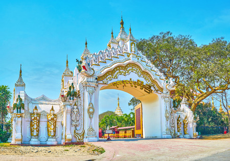 MANDALAY, MYANMAR - FEBRUARY 23, 2018: The beautiful side gates of the Kyauktawgyi Pagoda decorated with carved sculptures, on February 23 in Mandalay Editorial