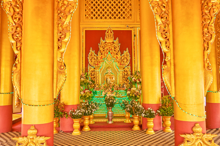 MANDALAY, MYANMAR - FEBRUARY 23, 2018: The gilden sculpture of Lord Buddga in gilden image house surrounded with the flowers in vases, on February 23 in Mandalay