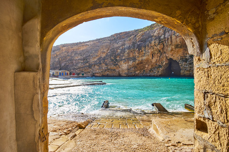 The view on Dwejra Inland sea and the Blue Hole grotto through the arch of the old boat house of San Lawrenz fishing village, Gozo Island, Malta.