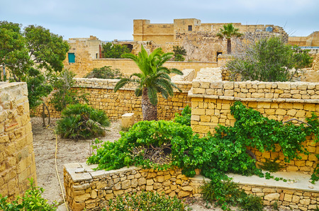 Walk the ramparts of Rabat Citadel and watch the ruins of old town with preserved stone walls and foundations, covered with lush greenery, Victoria, Gozo, Malta. Фото со стока