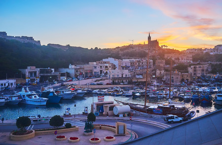 GHAJNSIELEM, MALTA - JUNE 15, 2018: The scenic fishing harbor with boats, rocky hills and tall silhouette of Parish Church on twilight, on June 15 in Ghajnsielem.