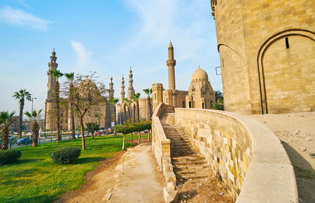 Walk along the porch of Bab Al-Azab Gate of Saladin Citadel with a view on green garden and tall minarets of the mosques in Salah El-Deen square (Sultan Hassan, Al Rifai and Al-Mahmoudia), Cairo, Egypt.
