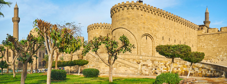 Panorama with a view on Bab Al-Azab Gate of outer wall of Saladin Citadel and green garden around it, Cairo, Egypt.