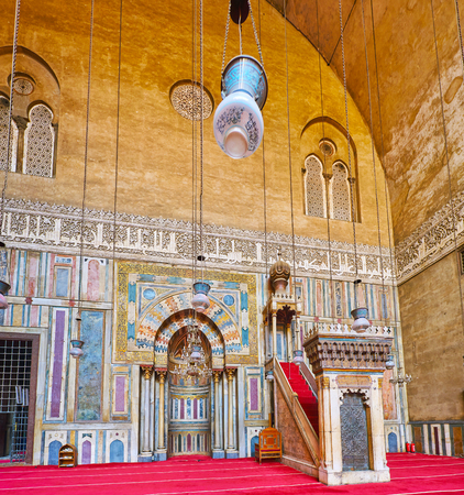 CAIRO, EGYPT - DECEMBER 21, 2017: The stunning summer prayer hall of Sultan Hassan Mosque-Madrasa with complex decorations of carved stone, stucco, gilt details and woodwork, on December 21 in Cairo