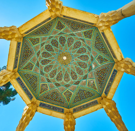 The scenic dome of Hafez Tomb pavilion with carved stone columns and ornate Islamic pattern of tile and mosaic, Shiraz, Iran. 免版税图像