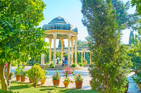 The scenic alcove of Hafez Tomb with carved stone columns and lush greenery of Mussala Gardens around it, Shiraz, Iran. 免版税图像