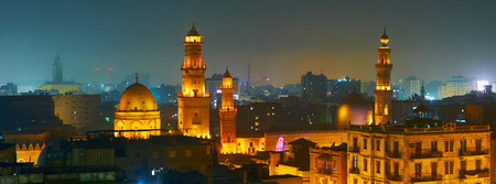 The brightly illuminated domes and minarets of Sultan Qalawun, Al Moez and Elzaher Barqooq Mosques in dark evening sky of Cairo, Egypt. Stock fotó