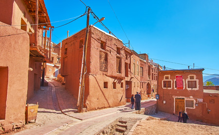 ABYANEH, IRAN - OCTOBER 23, 2018: Hilly streets of  the village are lined with traditional adobe houses, covered with red-ochre mud, that is visit card of this mountain settlement, on October 23 in Abyaneh