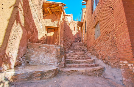 The old stone staircase in hilly backstreet between the red-ochre houses of historic Abyaneh village, Iran.