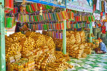 SAGAING, MYANMAR - FEBRUARY 21, 2018: The stalls of thanaka wood and bags for the logs in outdoor market of Kaunghmudaw Pagoda, on February 21 in Sagaing.