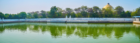 Panorama of old water tank of Kaunghmudaw Pagoda, surrounded by lush greenery behind the white wall, Sagaing, Myanmar.
