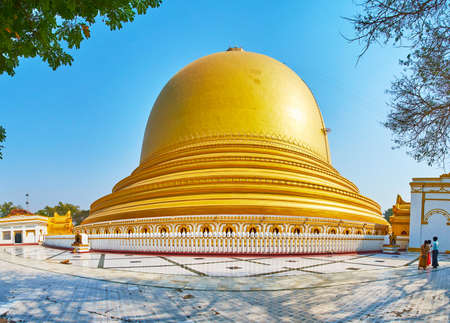 Panorama of magnificent golden Yaza Mani Sula Kaunghmudaw Pagoda, decorated by carved belts and surrounded by scenic relief fence, Sagaing, Myanmar.