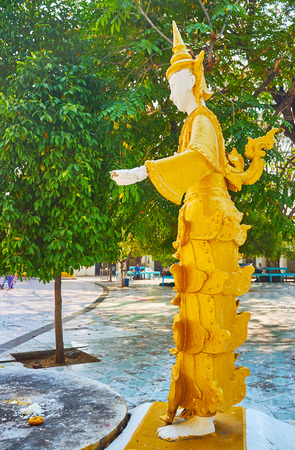 SAGAING, MYANMAR - FEBRUARY 21, 2018: The statue of Nat (spirit)  in traditional golden attire, located in garden of Yaza Mani Sula Kaunghmudaw Pagoda, on February 21 in Sagaing.