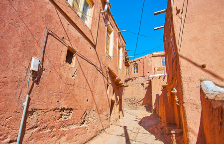 The narrow hilly street in Abyaneh mountain village with gutter in the middle of the road and old reddish adobe houses on both sides, Iran.