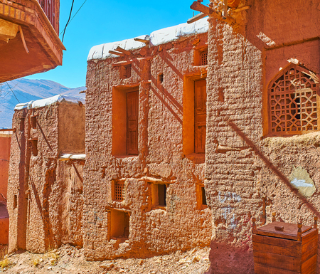The line of bright red-ochre houses, traditional for Abyaneh mountain village and preserved since olden days, Iran.