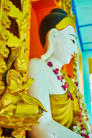 SAGAING, MYANMAR - FEBRUARY 21, 2018: The close-up of the Buddha image with small sculpture of praying golden Nat (Spirit-deity) on the foreground, U Min Thonze Temple, on February 21 in Sagaing Redactioneel