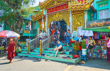 SAGAING, MYANMAR - FEBRUARY 21, 2018: The crowded entrance to Soon Oo Ponya Shin Pagoda (Summit Pagoda), people leave their footwear on the steps and go to the Shrine through the souvenir market, on February 21 in Sagaing