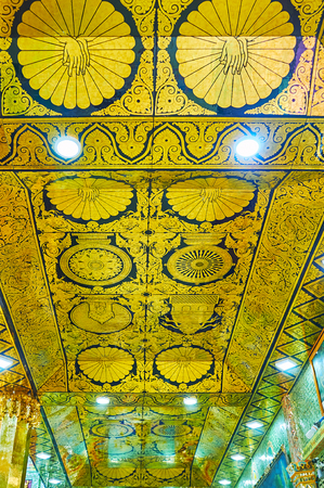 SAGAING, MYANMAR - FEBRUARY 21, 2018: The ceiling in Soon Oo Ponya Shin Pagoda (Summit Pagoda)with black-golden pannels, decorated with traditional Buddhist ornaments, on February 21 in Sagaing