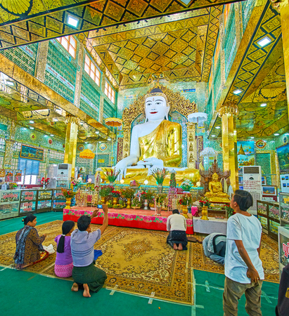 SAGAING, MYANMAR - FEBRUARY 21, 2018: The Buddhist pilgrims in Image House of Soon Oo Ponya Shin Paya (Summit Pagoda) with ornate interior anf giant Buddha statue, on February 21 in Sagaing Redakční