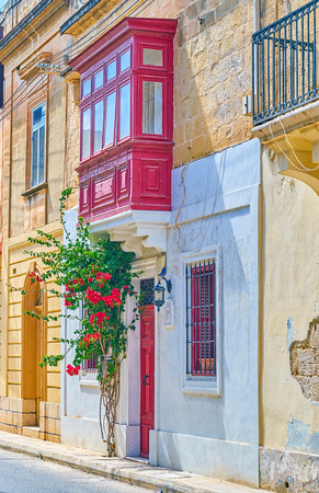The residential house in Mosta town with red door and Maltese style balcony, decorated with beautiful plant with red flowers