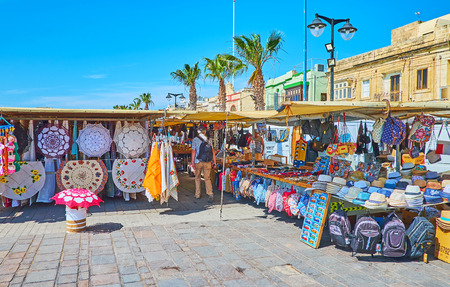 MARSAXLOKK, MALTA - JUNE 18, 2018: The tourist market occupies the part of seaside promenade and offers wide range of different souvenirs, traditional Maltese pieces and accessories, on June 18 in Marsaxlokk.