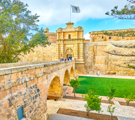 MDINA, MALTA - JUNE 14, 2018: The stobe arched bridge leading to the main (Vilhena) Gates of the Citadel, on June 14 in Mdina. Редакционное