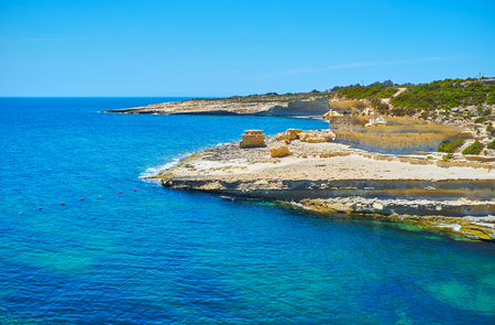 The picturesque rocks of Delimara peninsula attract the tourists to make the trips around it and visit St Peters Pool - the stunning beach on this area, Marsaxlokk, Malta. Imagens
