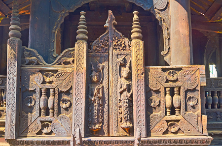 Decorative wooden gate with carved Nats (Spirits), floral patterns, small peacocks and myhical animals at the entrance to Bagaya Monastery, Ava, Myanmar.