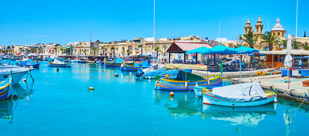 MARSAXLOKK, MALTA - JUNE 18, 2018: Panorama of marina, surrounded by old edifices, tourist cafes and market stalls, on June 18 in Marsaxlokk 에디토리얼