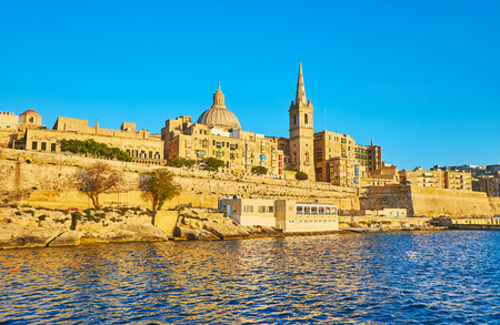 Enjoy the yacht trip along the medieval city walls of Valletta with a view on scenic bell tower of St Paul's Anglican Pro-Cathedral and the dome of Carmelite Church, Malta.