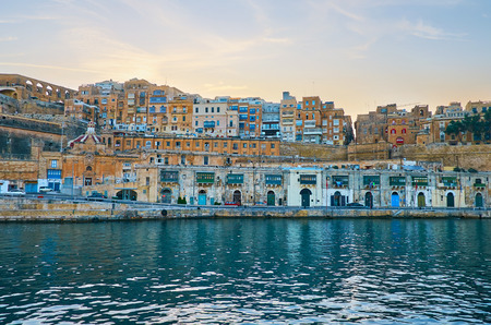 Watch Valletta from the Grand Harbour: the sinset sky over the line of old boat houses and warehouses stretches along Barriera and the old edifices are nested on the hill, Malta. Imagens