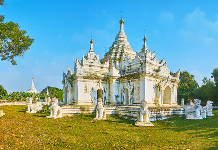 The white complex of Desada Taya Pagoda attracts tourists with its ornate carved decorations, interesting architecture and picturesque surroundings, Ava, Myanmar.