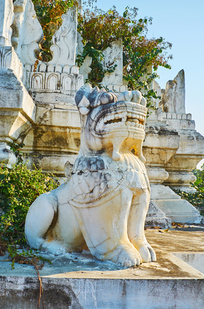 The carved leogryph (chinthe) is the mythical guardian of Buddhist temples, shrines and palaces, this white one sits at Desada Taya Pagoda, Ava, Myanmar. Stock Photo