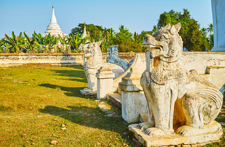 The old carved statues of chinthe - mythical Burmese leoryphs guard Desada Taya temple, the white pagoda of the complex is seen behind banana garden on the background, Ava, Myanmar.