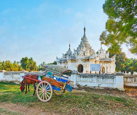 The vintage horse-drawned cart waits the tourists at the picturesque Desada Taya Pagoda - the ancient white temple of Ava (Inwa), Myanmar. Reklamní fotografie