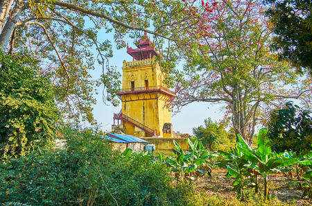 The view on the medieval Nanmyin Watchtower through the thickets of tropic garden with cotton tree, banana palms and other local plants, Ava, Myanmar.
